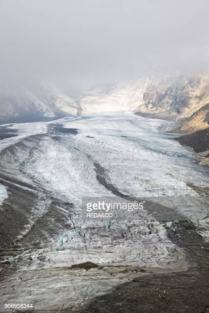 Glacier Pasterze of Mount Grossglockner with lateral and middle moraine and crevasses. Moraine debris on the surface of the glacier is insulating the...
