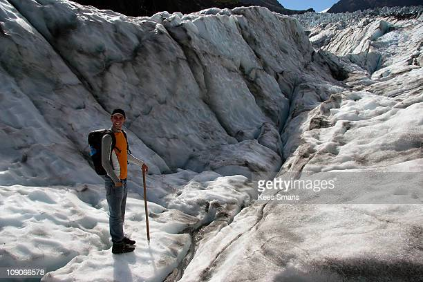Glacier Walk - Young man with backpack and icepick