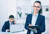 Glad business female secretary having cardboard in hands