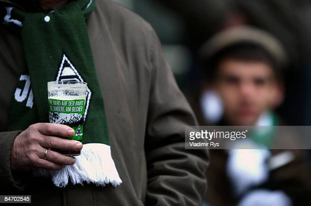 Gladbach fan holds a plastic glass with a beer during the Bundesliga game between Borussia Moenchengladbach and 1899 Hoffenheim at the Borussia Park...