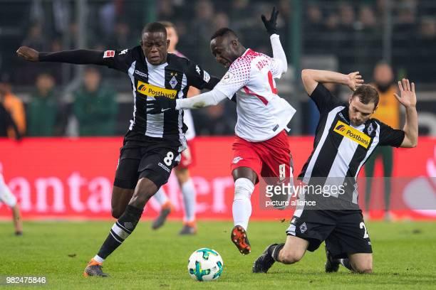 Gladbach's Denis Zakaria and Tony Jantschke vie for the ball with Leipzig's Naby Keita during the German Bundesliga football match between Borussia...
