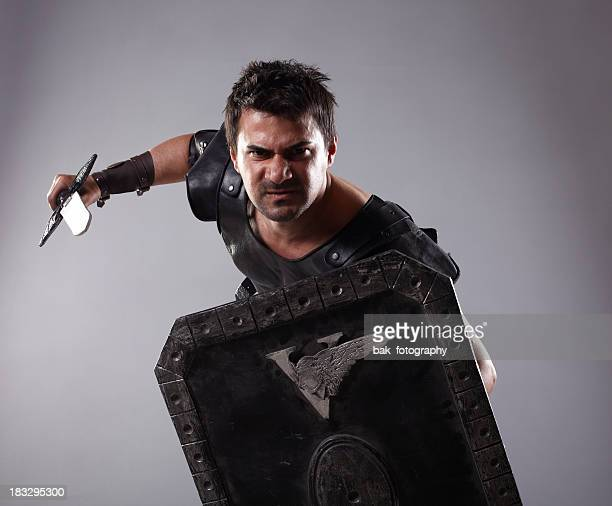 a gladiator holding an armor and a blade  - gladiator stock photos and pictures