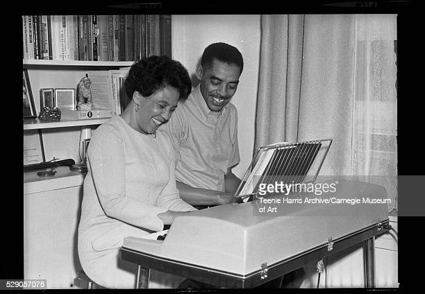 Gladys Coffee Harper and Thomas H Harper playing electric organ with music from 'The Methodist Hymnal' in living room of their apartment in Shadyside...