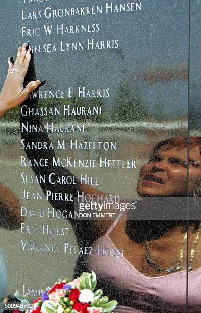 Gladys Lopez reaches up to touch a name on the memorial for TWA Flight 800 on Monday 17 July 2006 at Smith Point Park in Shirley New York on the 10th...