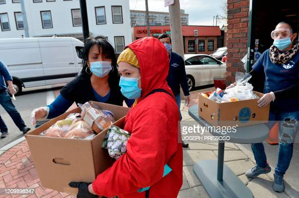 Gladys Vega Executive Director of the Chelsea Collaborative Inc helps directing people in line in an effort to distribute food and packages of...