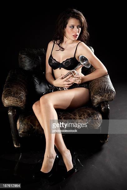 Glamour beauté assise sur une chaise avec la trompette