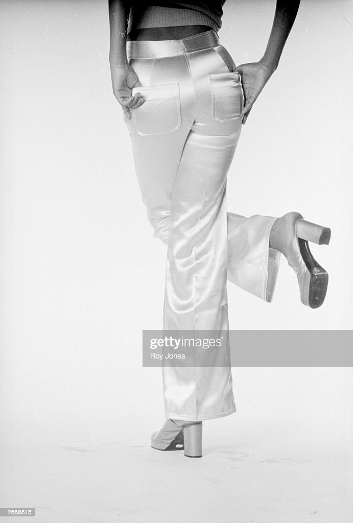 Glamorous 1970's satin trousers worn with high-heeled clogs.