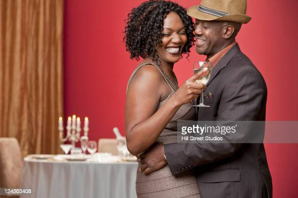 Glamorous African American couple drinking white wine