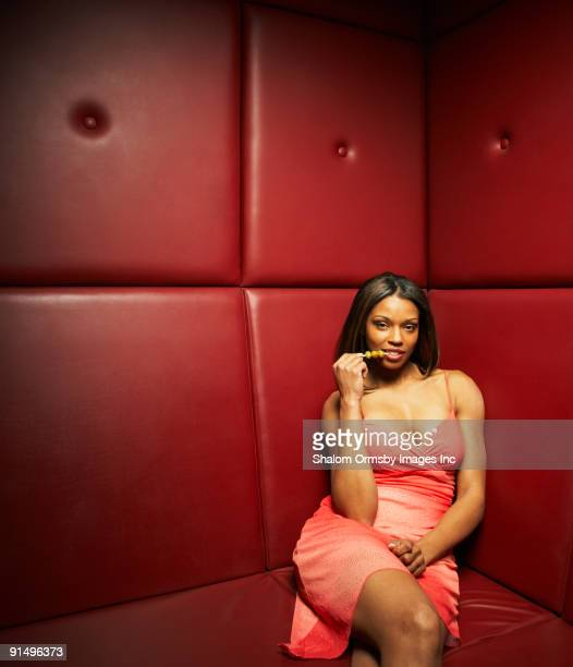 Glamorous African woman eating olives in nightclub