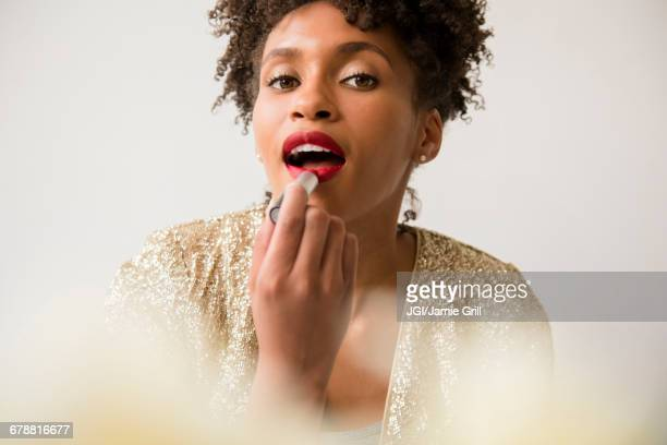 glamorous black woman applying red lipstick - lipstick stock pictures, royalty-free photos & images