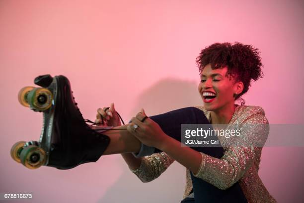 glamorous black woman tying roller skate - roller skating stock photos and pictures