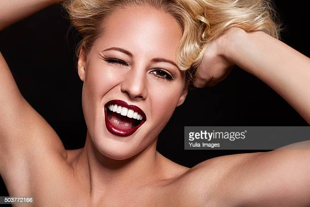Glamorous Blond Woman Winking with Hands in Hair