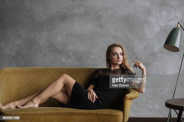 glamorous caucasian woman sitting on sofa - lace dress stock pictures, royalty-free photos & images