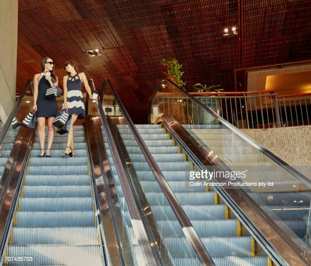 Glamorous friends riding escalator in shopping mall