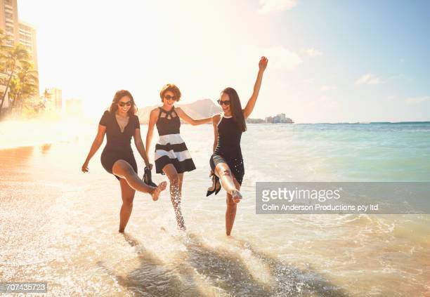 Glamorous friends splashing on ocean waves