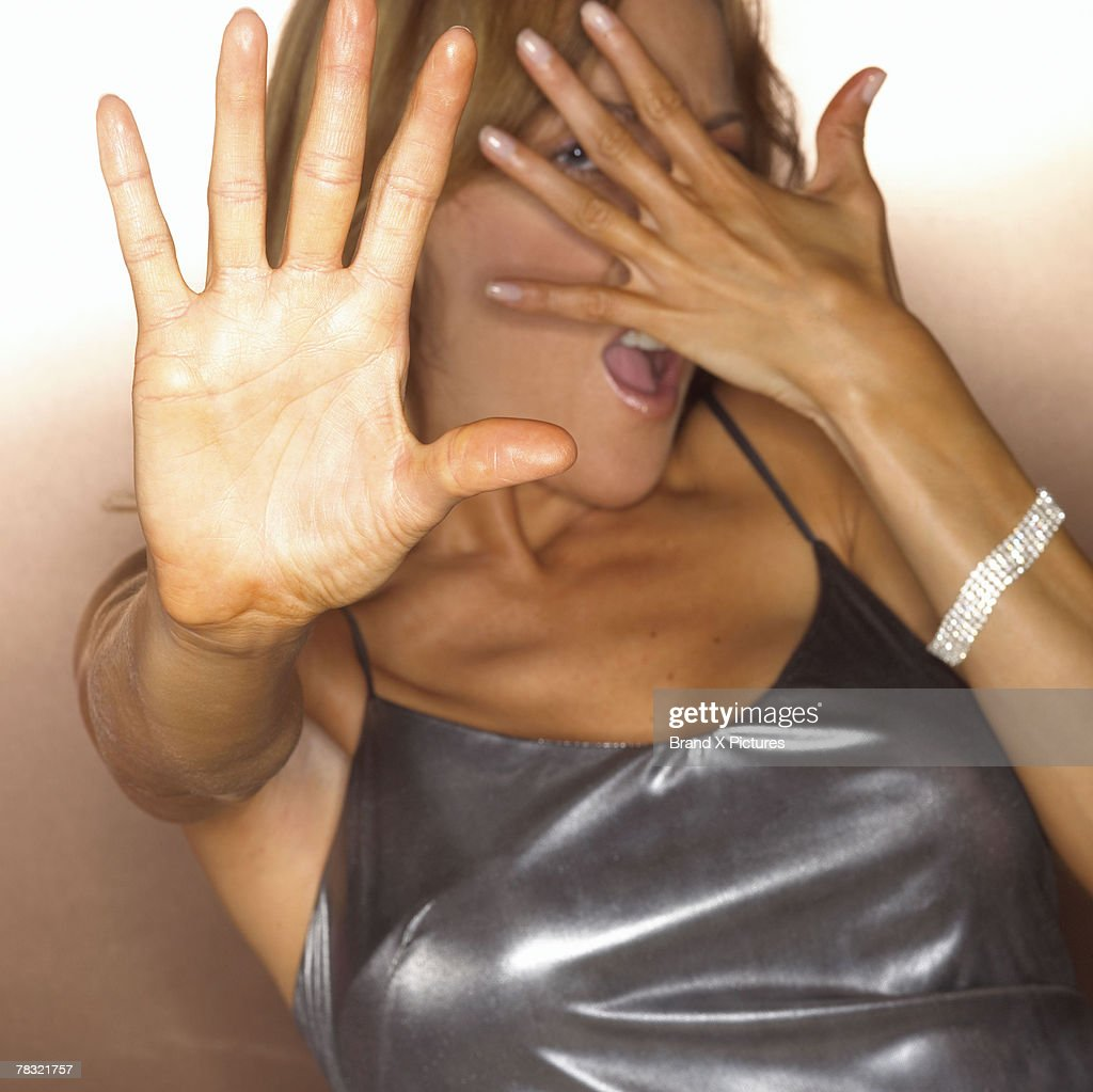 Glamorous girl hiding face with her hand : Stock Photo