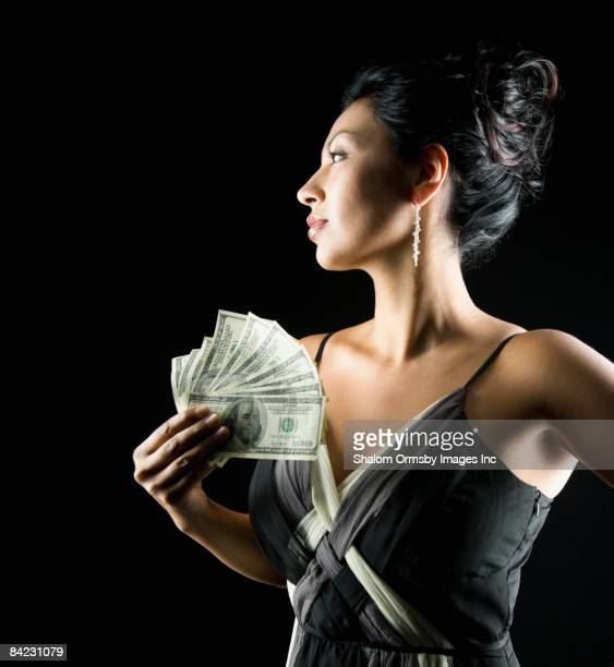 glamorous hispanic woman holding money - may december romance stock photos and pictures