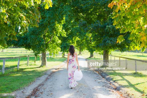 glamorous hispanic woman walking on park path - zwart haar stockfoto's en -beelden