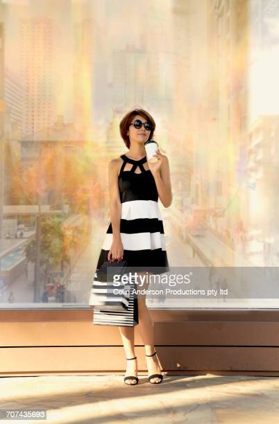 Glamorous Japanese woman on sidewalk holding coffee and shopping bags