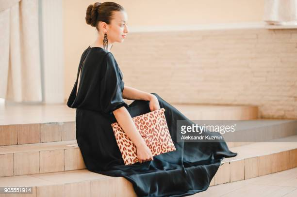 glamorous middle eastern woman sitting on staircase holding purse - animal pattern stock pictures, royalty-free photos & images