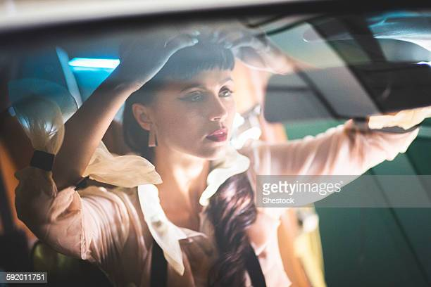 Glamorous mixed race woman checking hair in car mirror