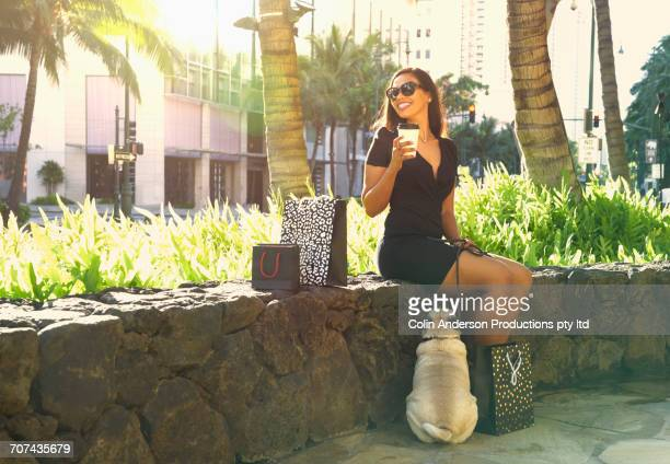 Glamorous Mixed Race woman sitting on stone wall drinking coffee