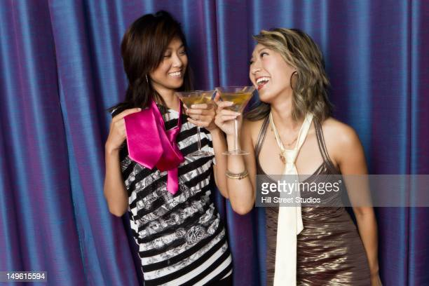 Glamorous mixed race women drinking cocktails