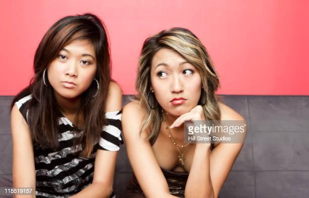 Glamorous mixed race women sitting on sofa
