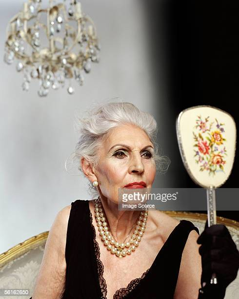 Glamorous senior woman looking at herself in hand mirror