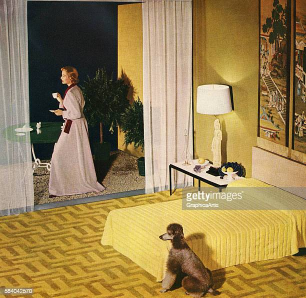 A glamorous single woman enjoys a cup of coffee with her poodle standing on the balcony of her spacious apartment's bedroom 1950 Screen print after a...