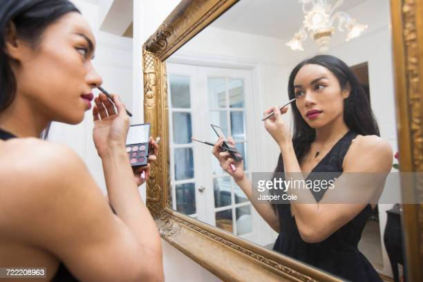 Glamorous transgender Thai woman applying eyeliner in mirror