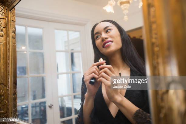 glamorous transgender thai woman applying lipstick in mirror - gender fluid stock photos and pictures