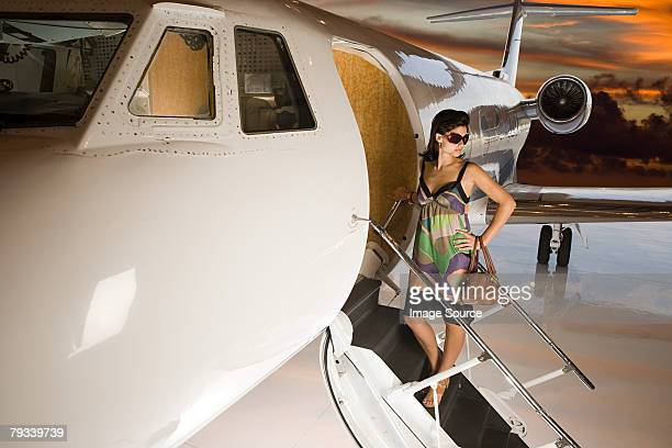 Glamorous woman by private airplane