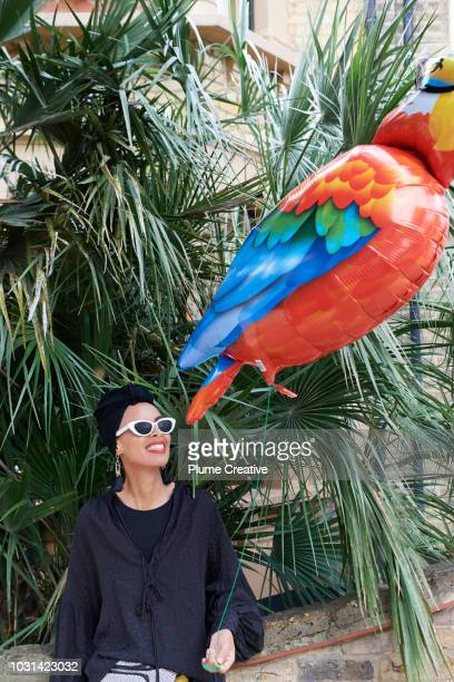 Glamorous woman holding a parrot balloon