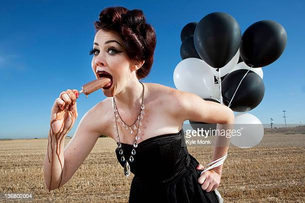 Glamorous woman holding balloons and eating popsicle