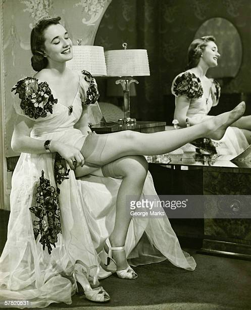 Glamorous woman in evening gown putting on silk stockings, (B&W)