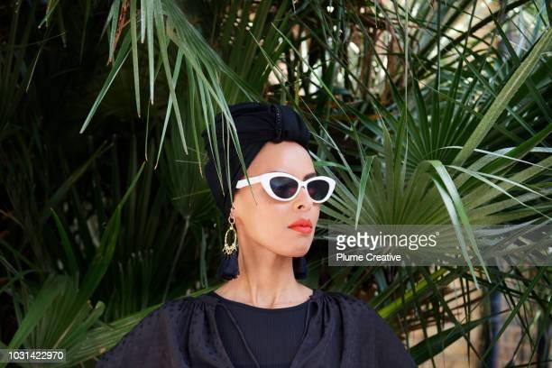 Glamorous Woman in sunglasses in tropical scene