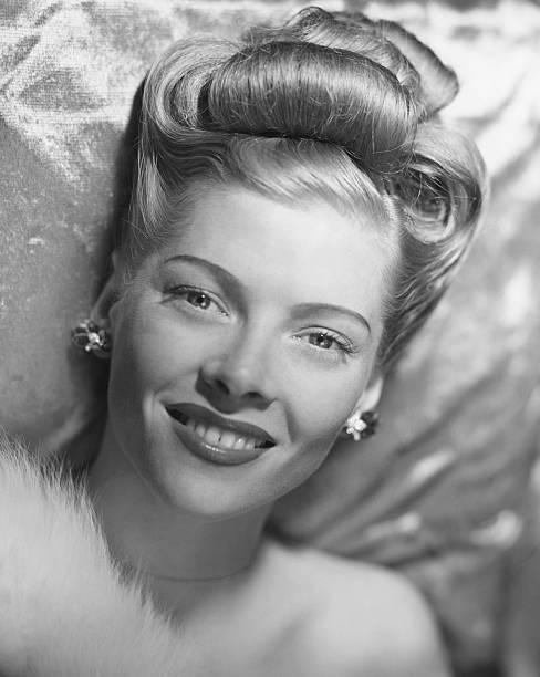 Glamorous woman lying on satin pillow, (B&W), portrait