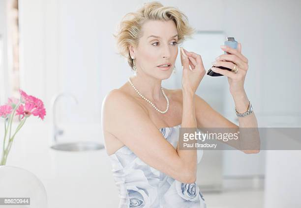 glamorous woman putting on makeup - strapless dress stock pictures, royalty-free photos & images