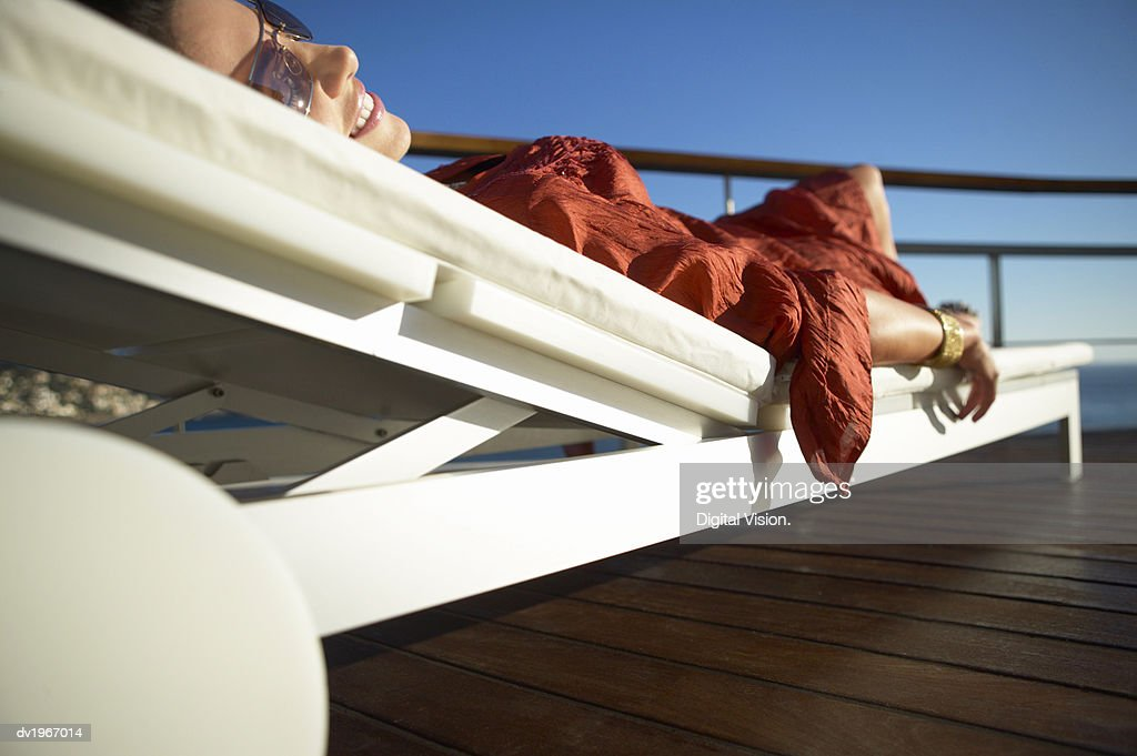 Glamorous Woman Relaxing on a Sun Lounger : Stock Photo