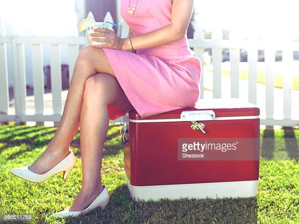 glamorous woman sitting on vintage cooler in backyard - esky stock photos and pictures