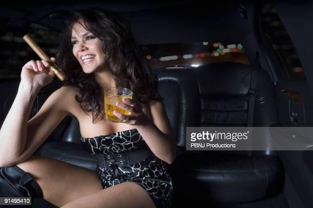 Glamorous woman smoking cigar in backseat of limousine