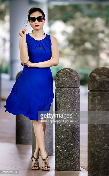 Glamorous Woman Standing By Bollards On Sidewalk