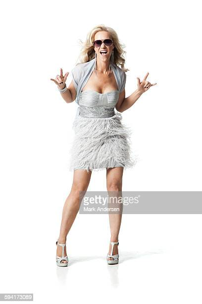Glamorous woman standing in studio making hand gesture