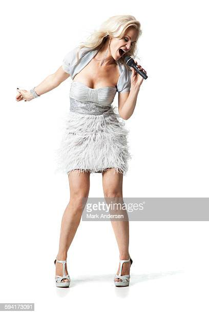 Glamorous woman standing in studio singing into microphone