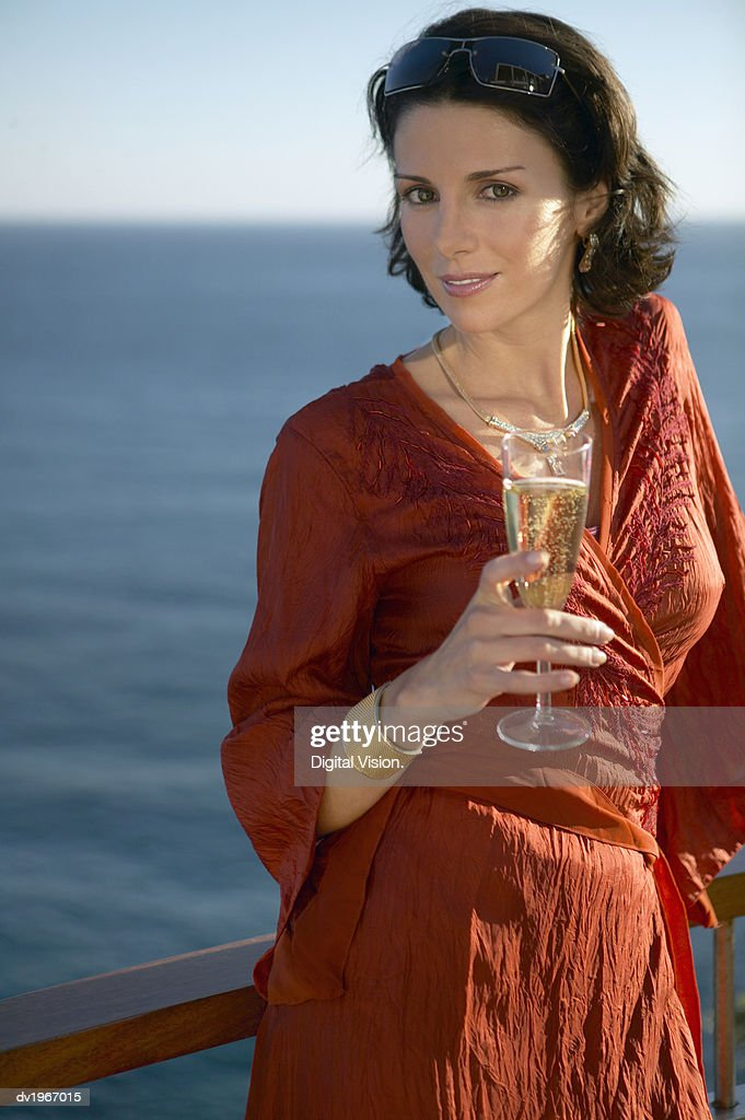Glamorous Woman Wearing a Red Dress and Holding a Glass of Champagne, with the Sea in the Background : Stock Photo