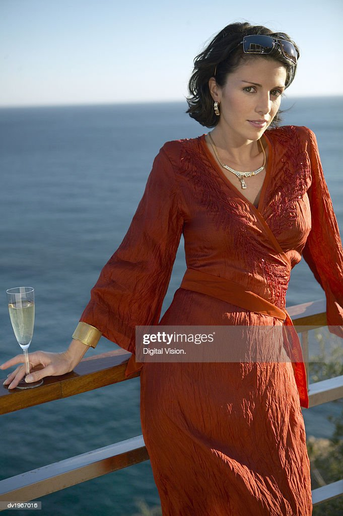 Glamorous Woman Wearing a Red Dress Leaning Against a Railing, with the Sea in the Background : Stock Photo