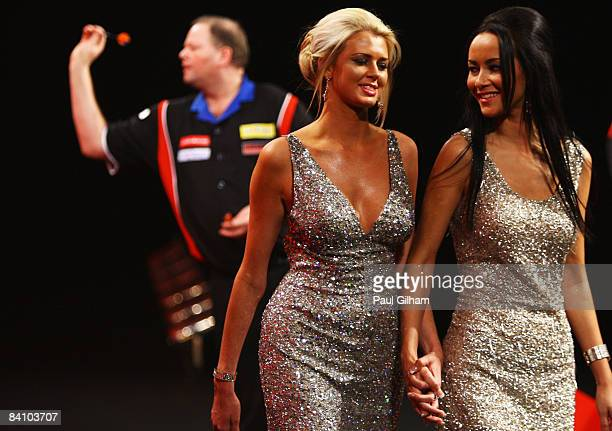 Glamour girls leave the stage as Raymond van Barneveld throws a dart during the first round match between Raymond van Barneveld of Netherlands and...