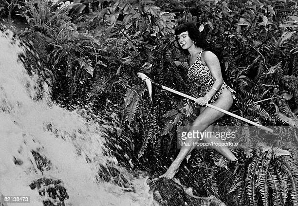 1954 American pinup glamour model Bettie Page born Nashville Tennessee pictured here in a posed shot spearfishing by a waterfall while on a modelling...