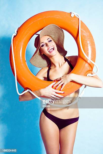 Glamour portrait of woman posing with a lifebuoy